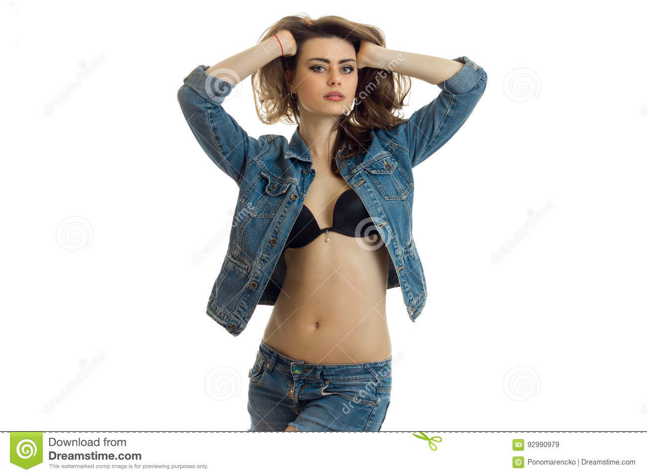 young girl in black bra and with unfastened denim jacket keeps hands and hair looks straight