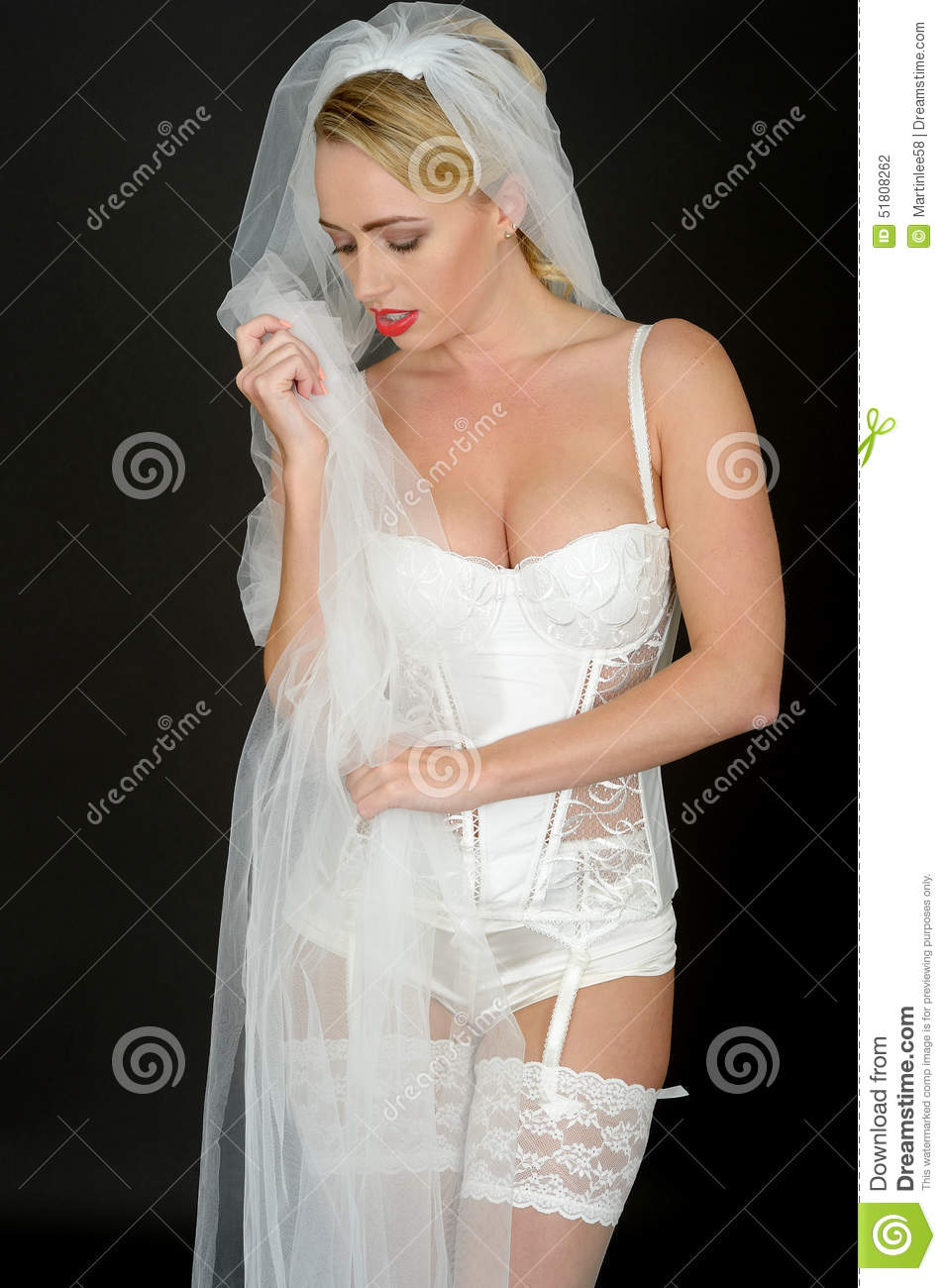 64ca7095ea2 A DSLR royalty free image of a pretty, attractive young bride, wearing a  white corset, veil suspender belt and stockings, in a thoughtful serious  mood, ...