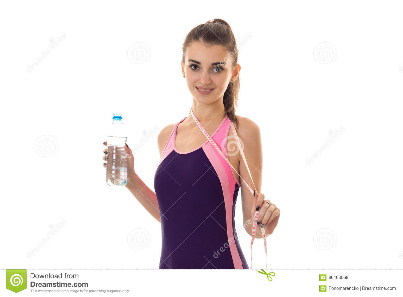 young woman with bottle water and measure tape in magenta body swimsuit  smiling on camera isolated on white.