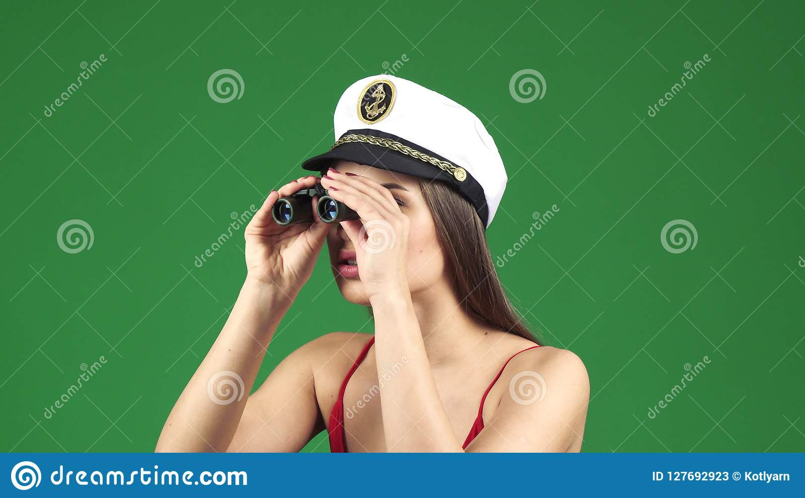 1b5a987e4b5 Close up of a happy young beautiful woman looking away using binoculars  wearing sailor cap smiling seductively to the camera on green chromakey  background ...