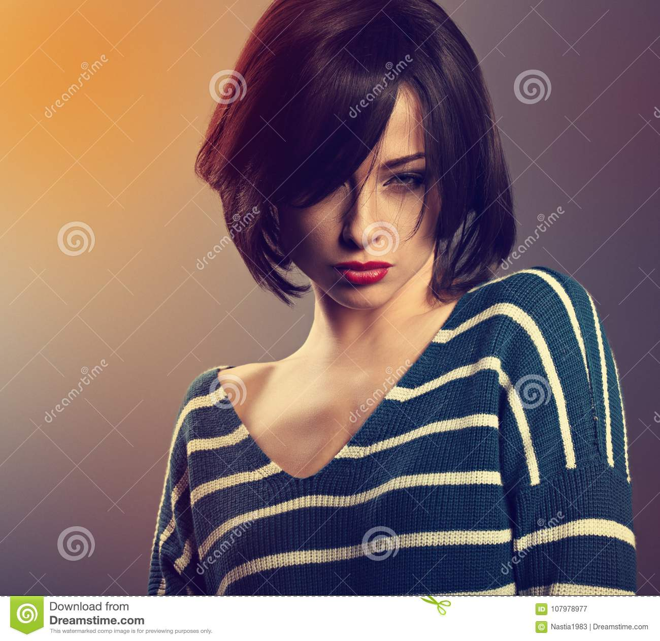 Young Woman With Short Hair In Fashion Sweater Posing On Gr Stock