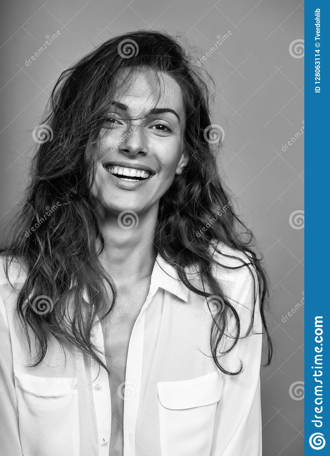 07f051f654 Young woman with pretty face and long brunette curly hair in white shirt  has slim body in studio on grey background