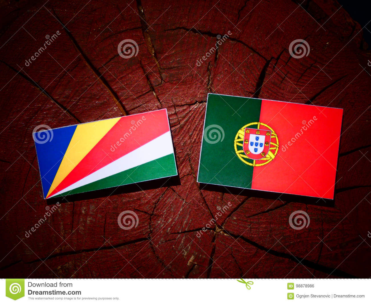 Seychelles flag with Portuguese flag on a tree stump isolated