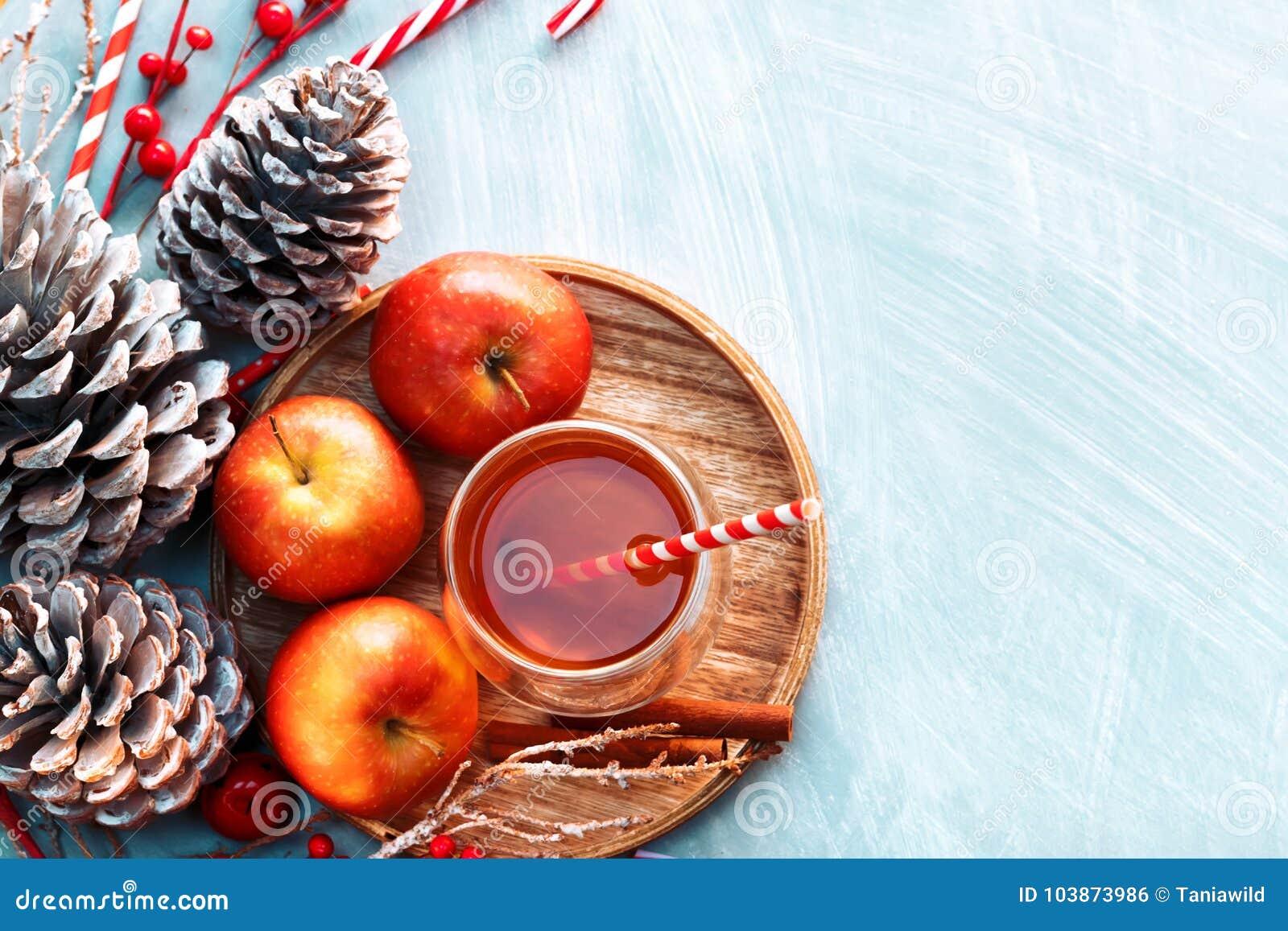 Sezonowy i wakacje pojęcie Zimy gorąca herbata w szkle z jabłkami i pikantność na drewnianym tle Selekcyjna ostrość, odgórny wido