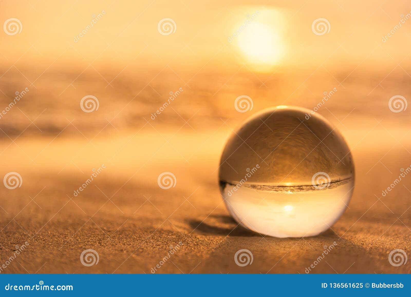 Sfera di cristallo sulla spiaggia con le onde del mare ad alba di mattina thailand
