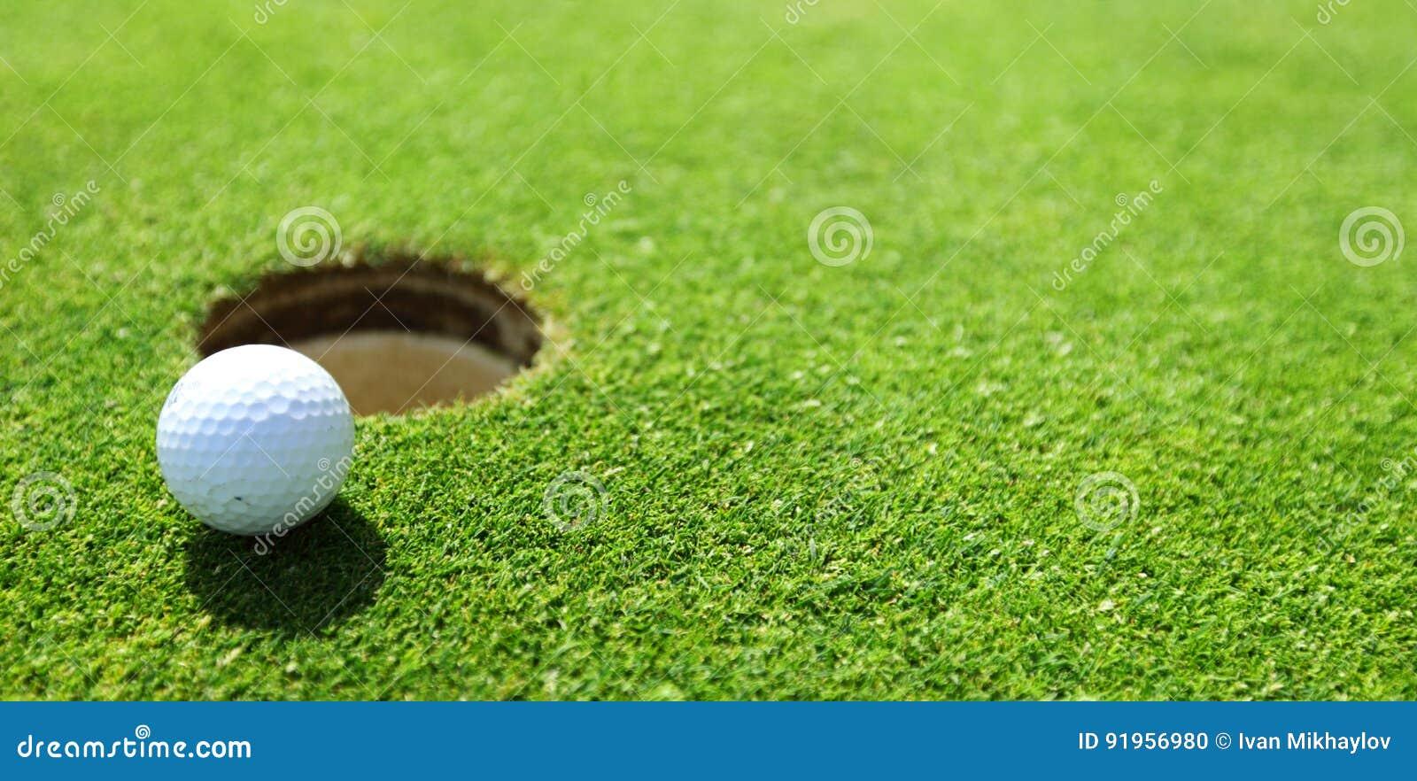 Sfera di golf sull orlo della tazza