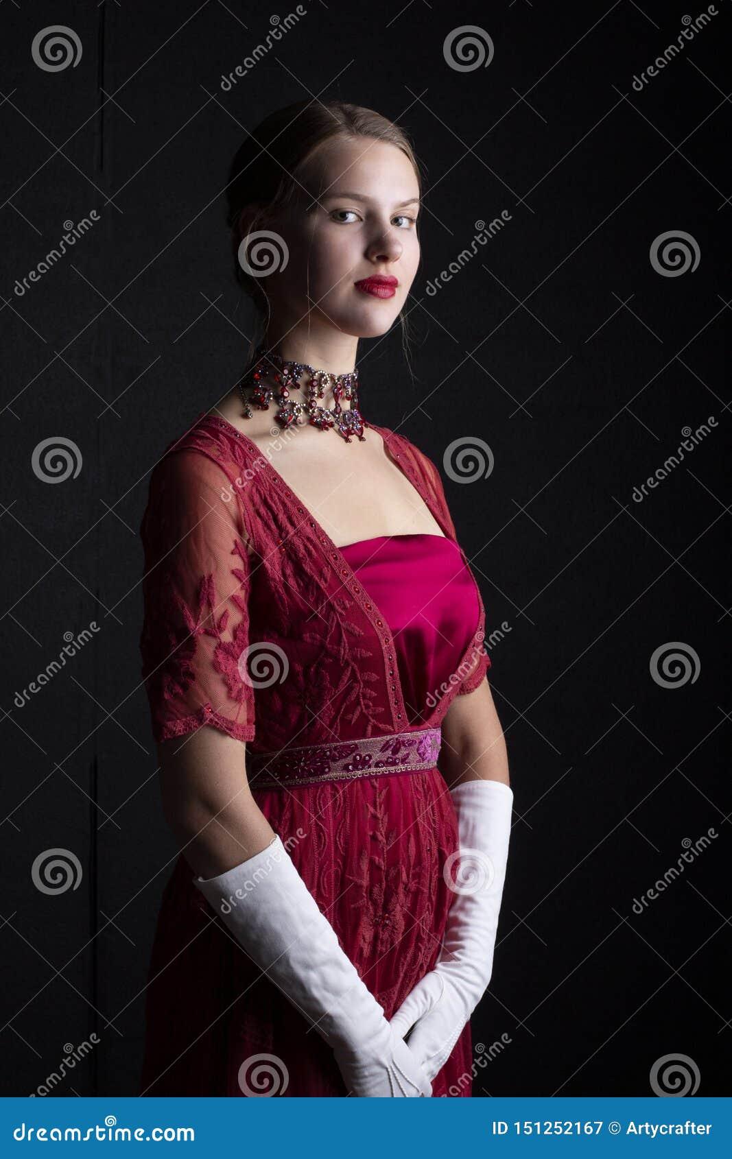 1910 sfrau im roten Spitzekleid und in der Kristallhalskette