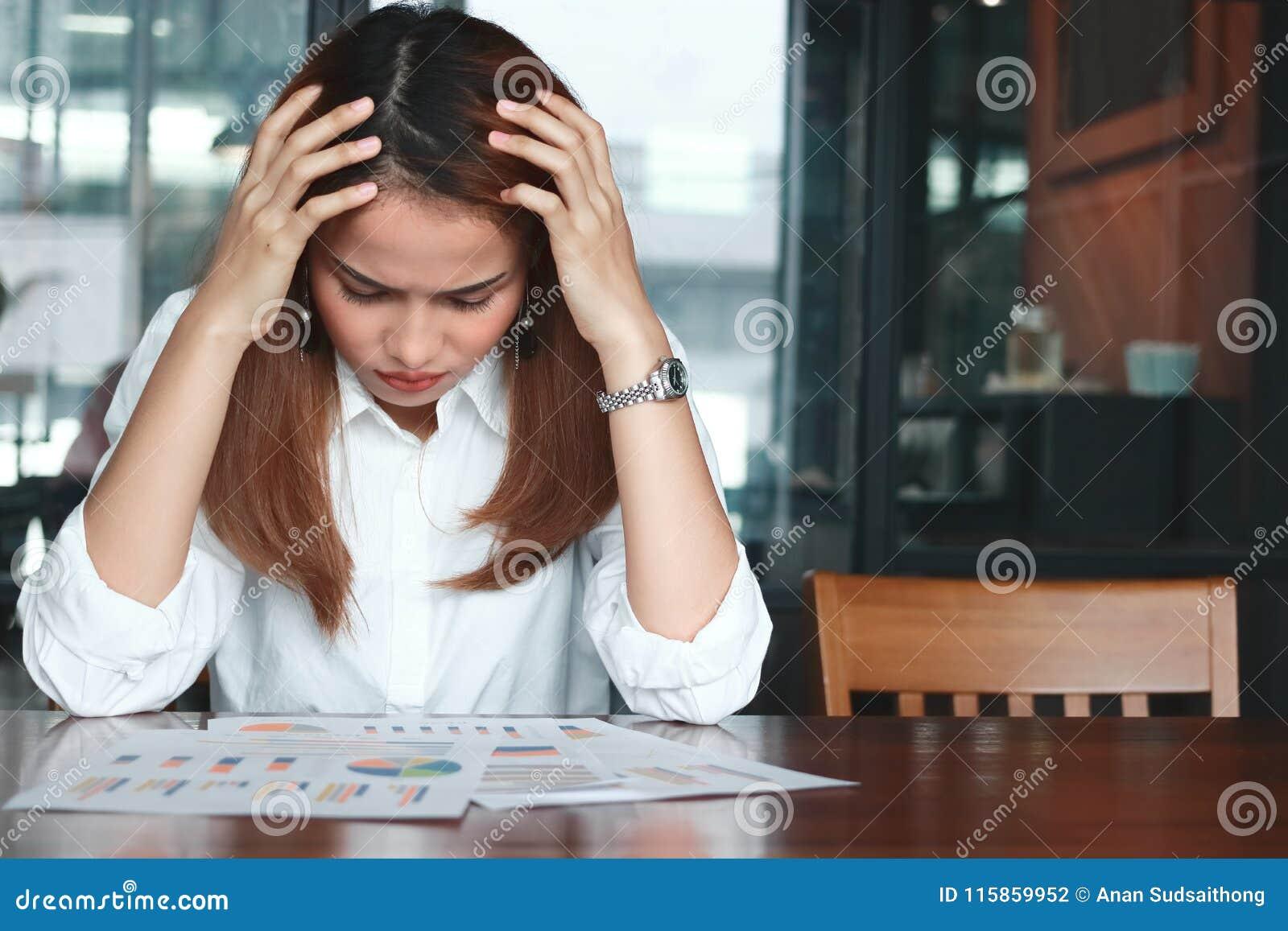Sfrustowana zaakcentowana młoda Azjatycka biznesowa kobieta analizuje papierkową robotę lub mapy w miejscu pracy Myślący i rozważ