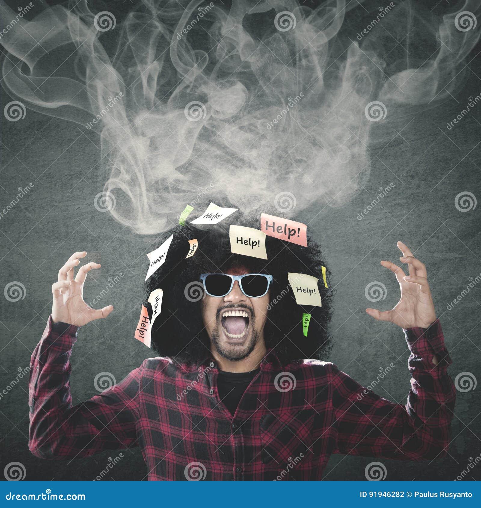 Sfrustowany Afro mężczyzna z dymem na głowie