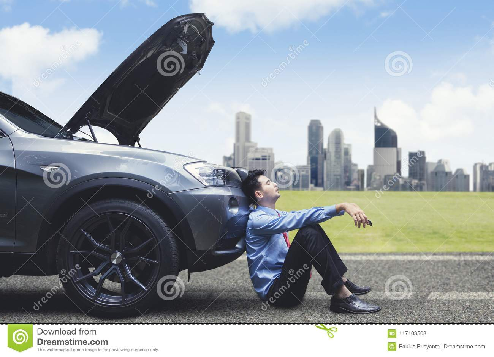 Sfrustowany biznesmen opiera na łamanym puszka samochodzie