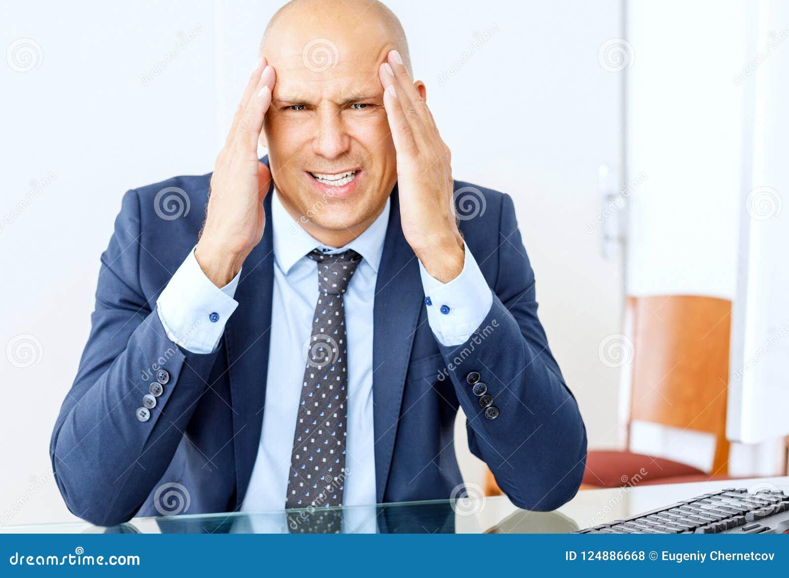 Sfrustowany biznesowy mężczyzna pracuje przy biurowym wnętrzem