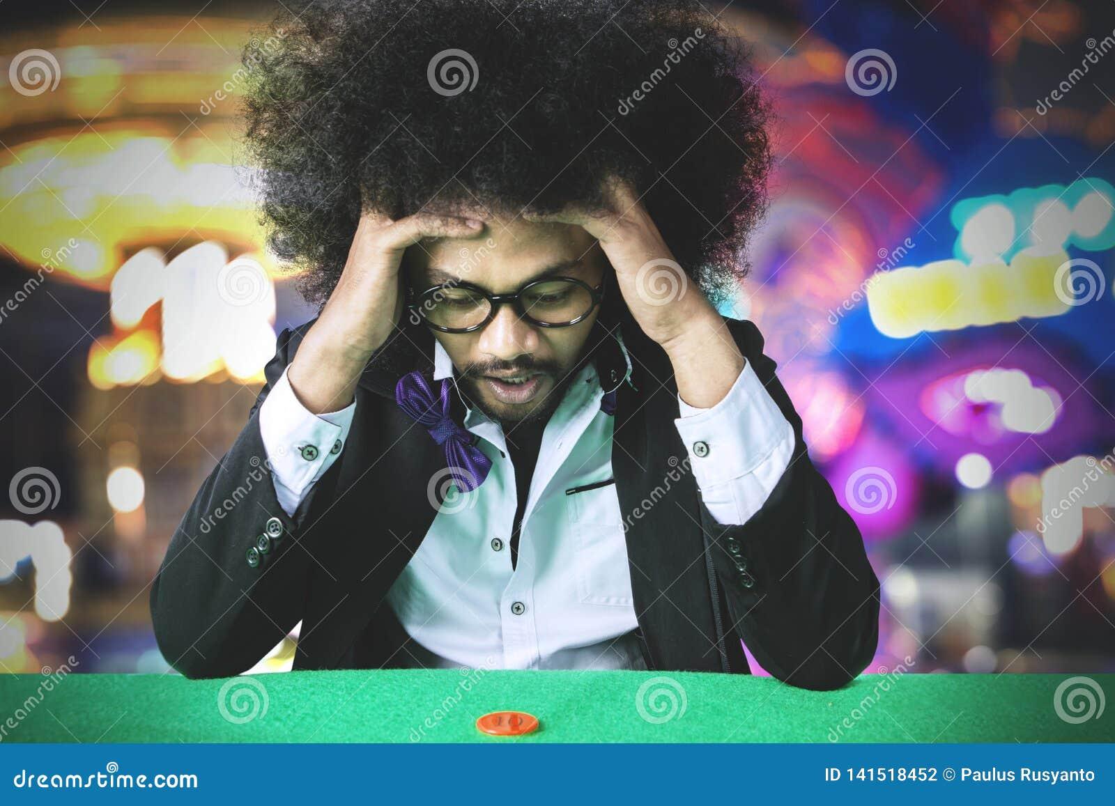 Sfrustowany hazardzisty mężczyzny przegrywanie na hazardzie