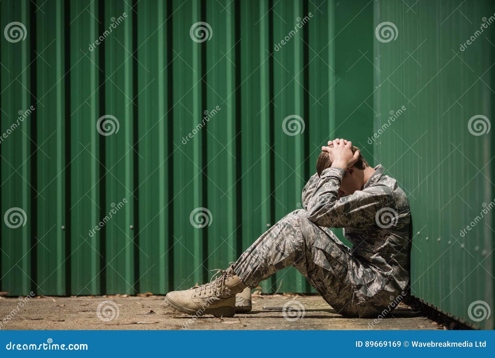 Sfrustowany militarny żołnierza obsiadanie z rękami na głowie