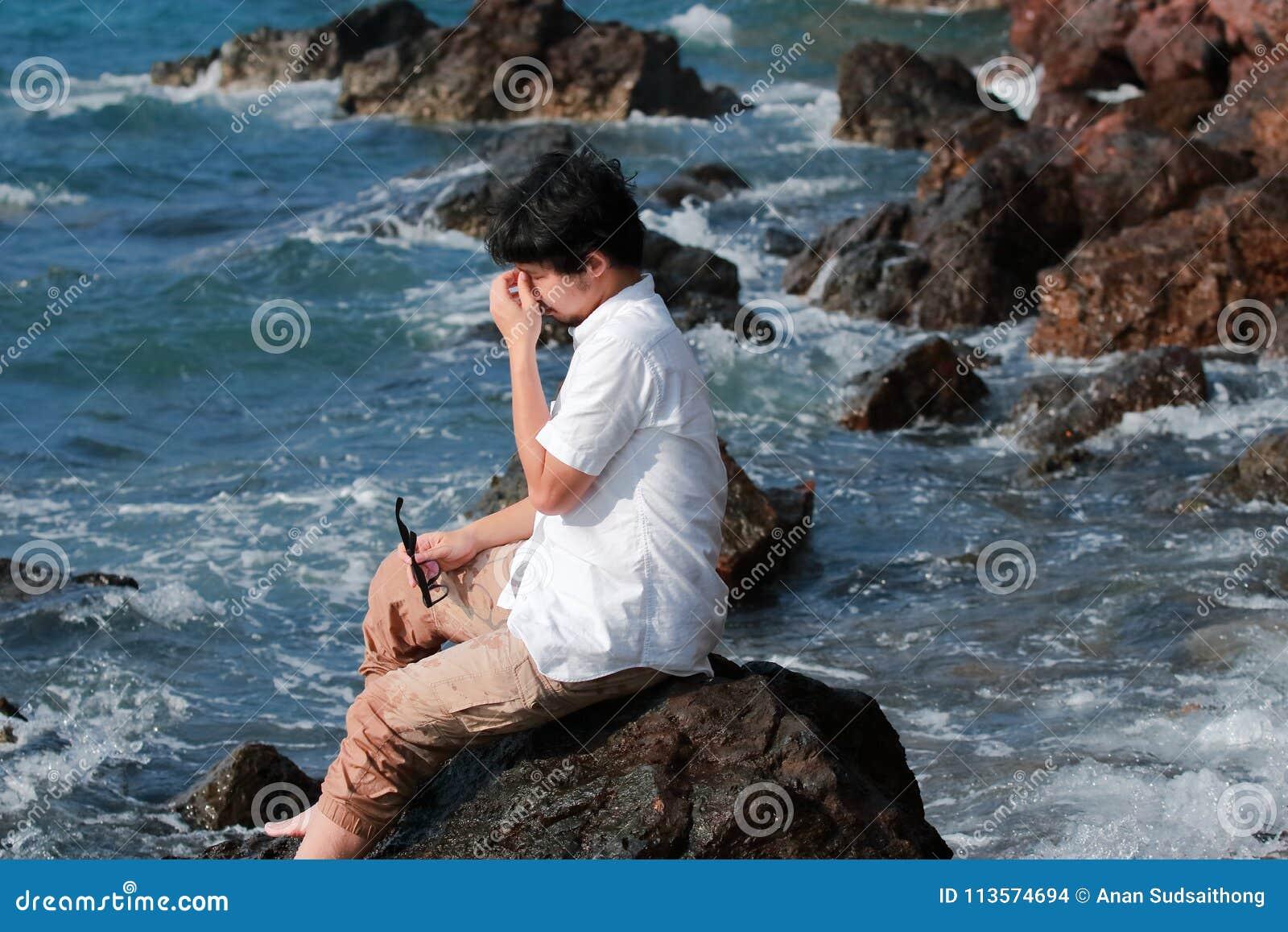 Sfrustowany wzburzony młody Azjatycki mężczyzna bierze daleko szkła i zamyka jego oczy przy dennym wybrzeżem