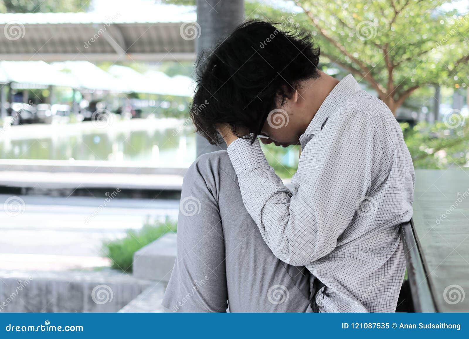 Sfrustowany zaakcentowany młody Azjatycki biznesowego mężczyzna uczucie rozczarowywający lub wyczerpujący z pracą przy outside bi