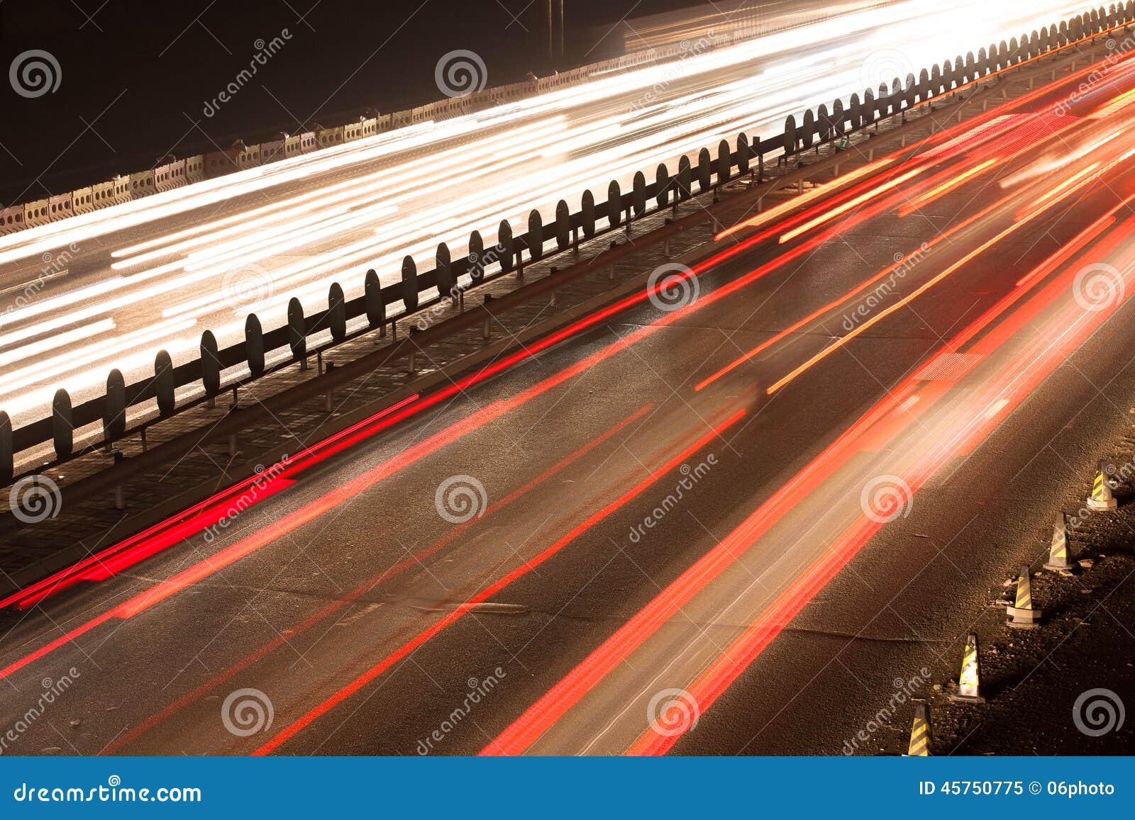 Sfuocatura di movimento occupata di traffico di notte