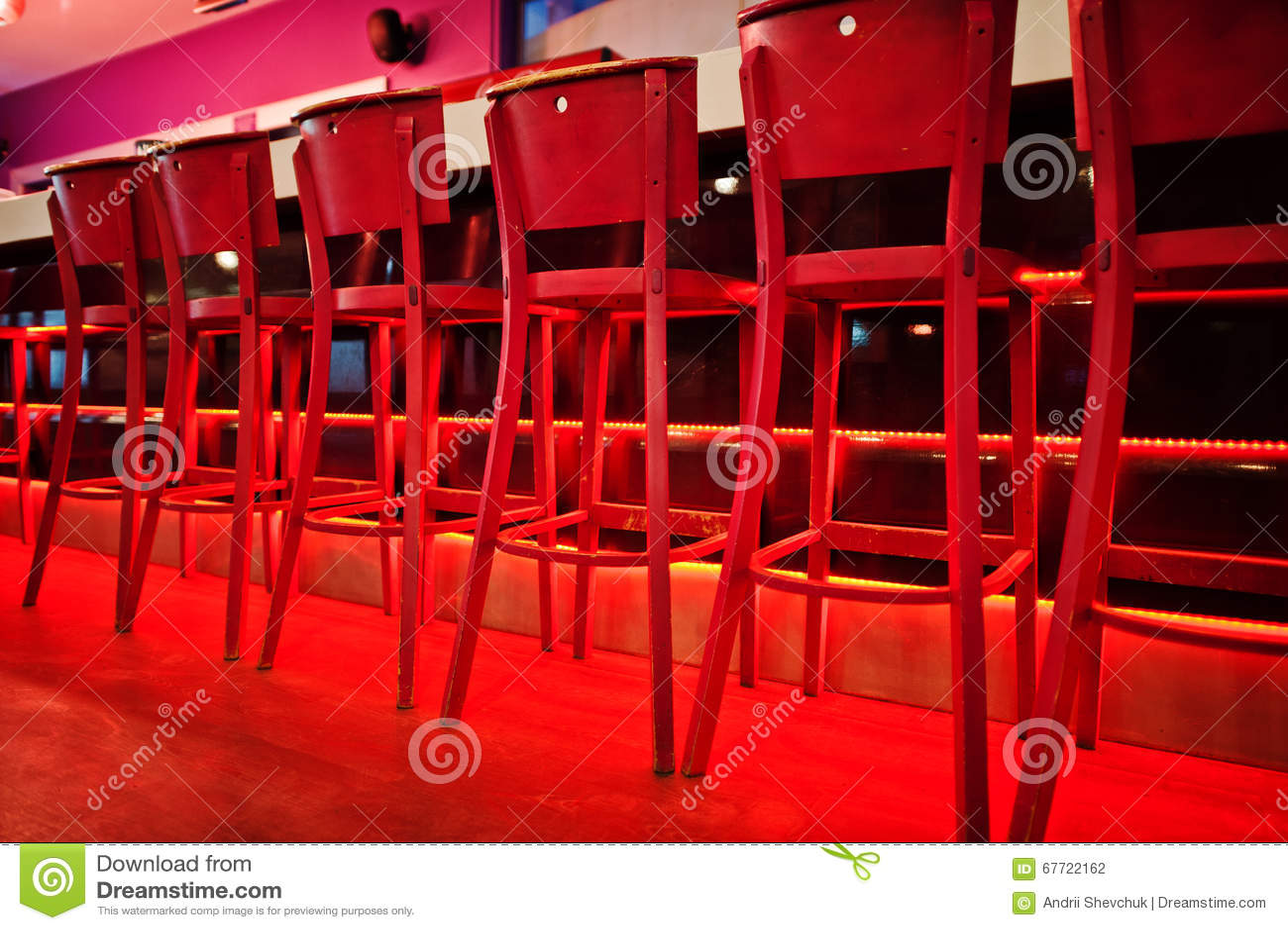 Sgabelli da bar rossi alla luce di colore del diodo fotografia