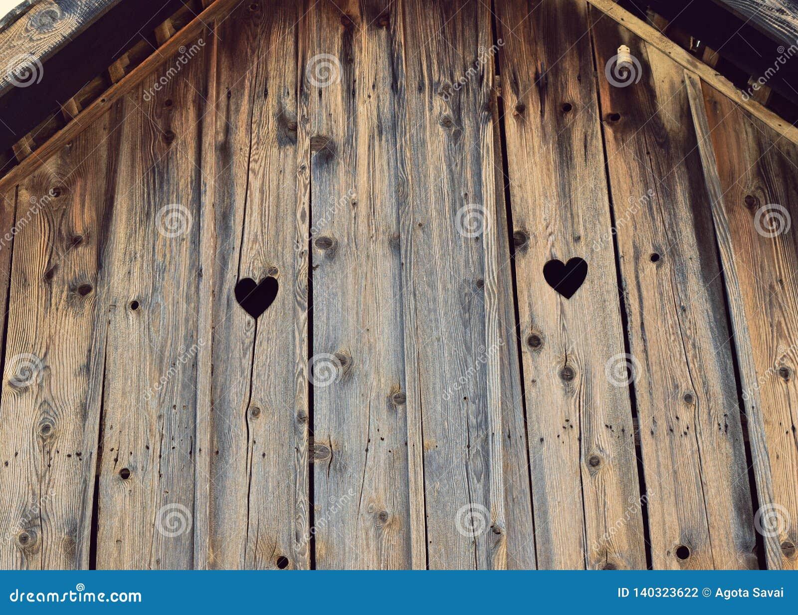 Sguardo di forma del cuore fuori sulla vecchia casa di legno Amore, candeggiato 103 anni