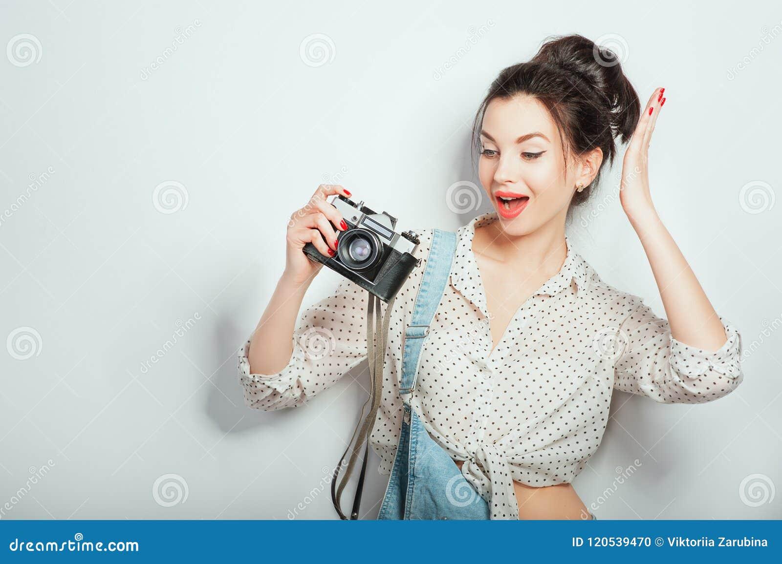 Sguardo di modo, modello abbastanza fresco della giovane donna con la retro macchina fotografica che dura in vestiti del denim ch