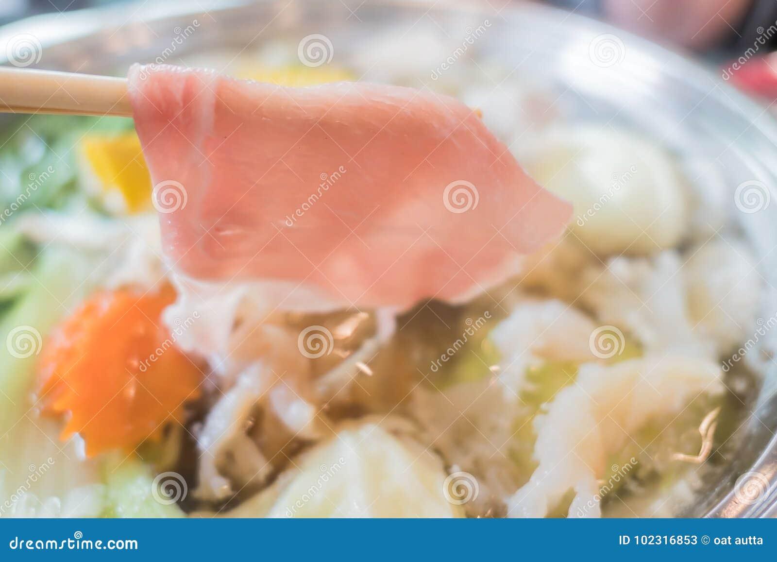 Shabu Shabu или Sukiyaki или горячий бак, рука держа свинину используя палочки, японскую еду в ресторане