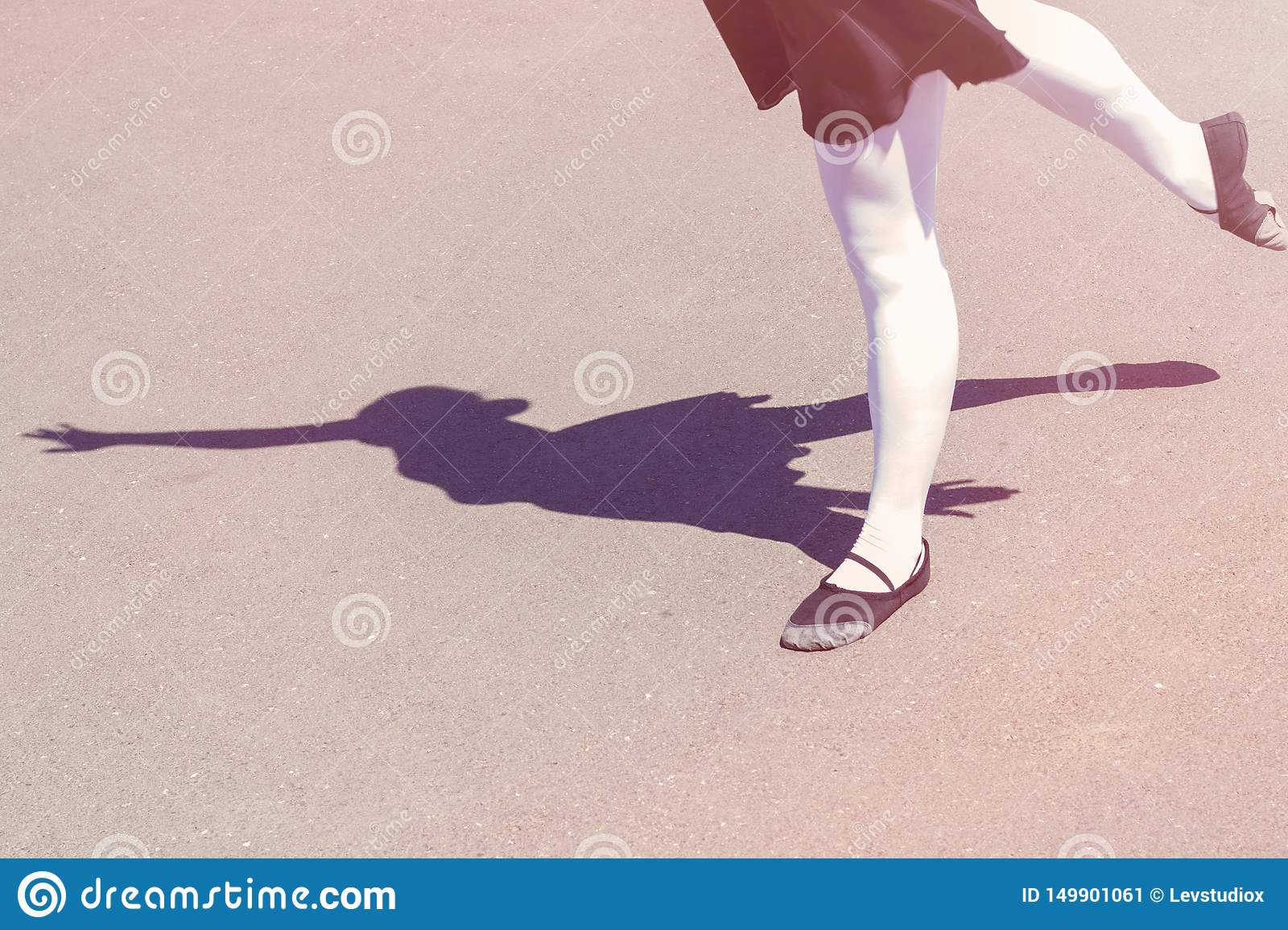 Shadow of dancer girl which makes dance moves in a bathing suit for dancing and ballet shoes