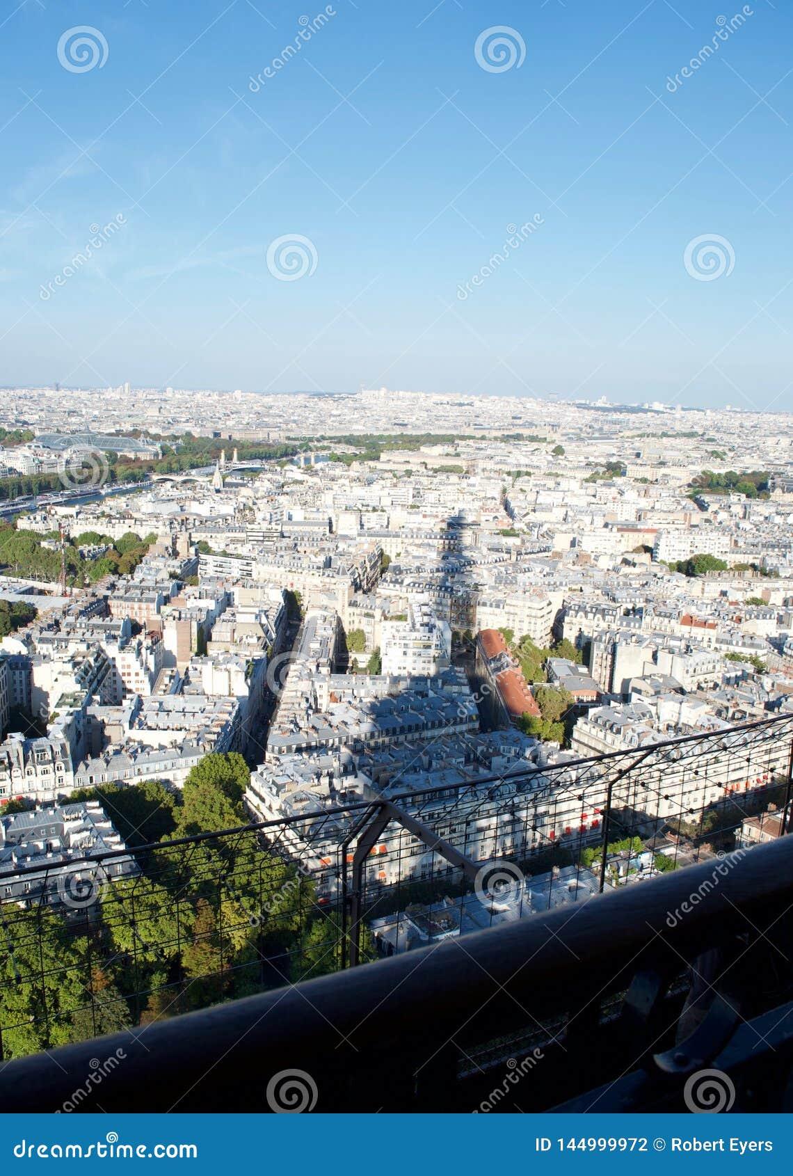 Shadow of Eiffel tower on sunlit Paris France below