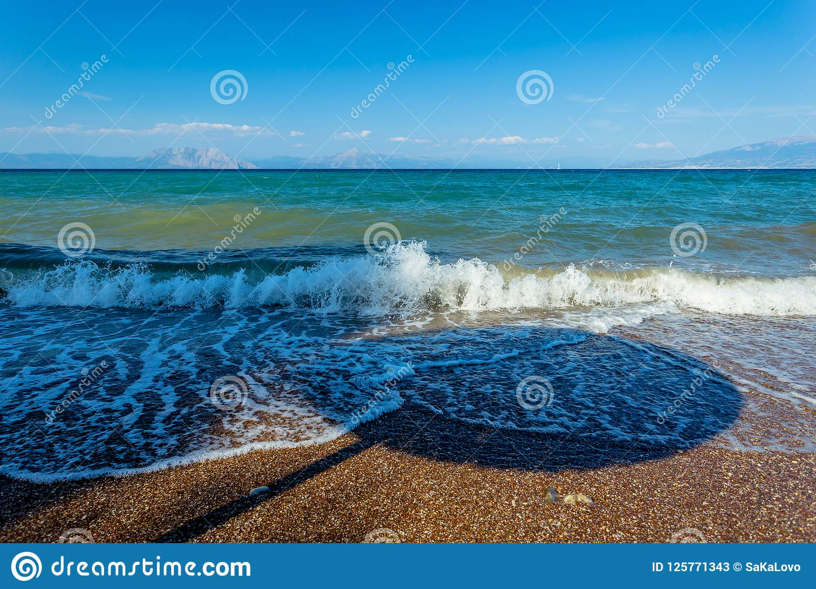 Shadow Of A Parasol In Waves On A Greek Pebble Beach Stock