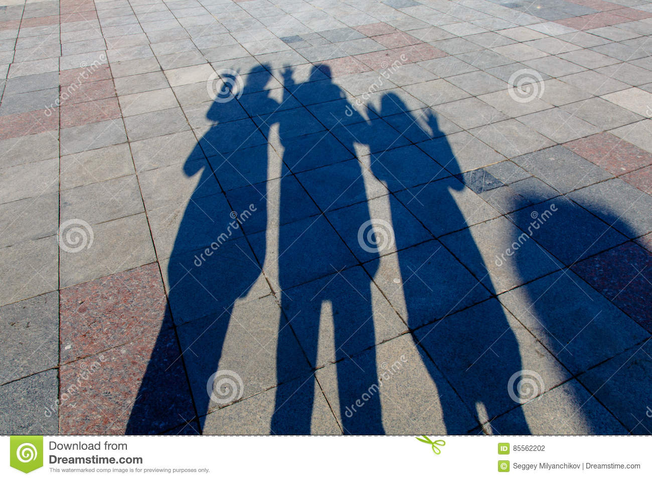 The Shadows Of Three People On A Pavement Tiles Stock