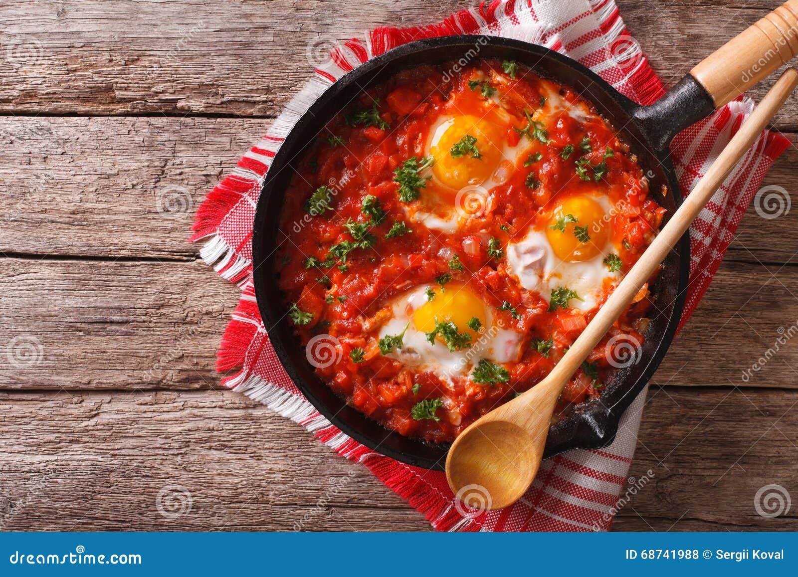 Shakshuka-Frühstück von Spiegeleiern und von Tomaten in einer Wanne horizont