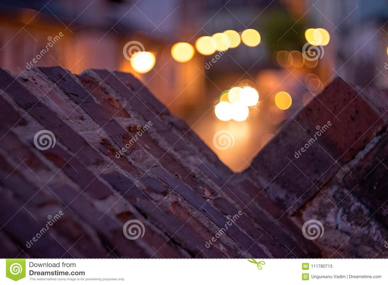 Shallow depth of field and close up of an medieval brick wall at sunrise with nice colors in background