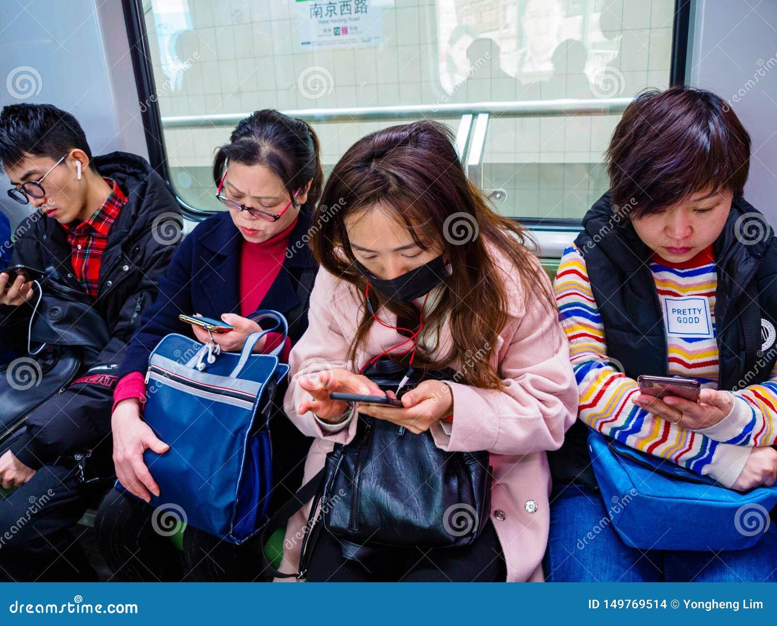 SHANGHAI, CHINA - 12. MÄRZ 2019 - eine Reihe von Pendlern auf der Shanghai-Metro alle auf ihren Smartphones China hat ein extrem