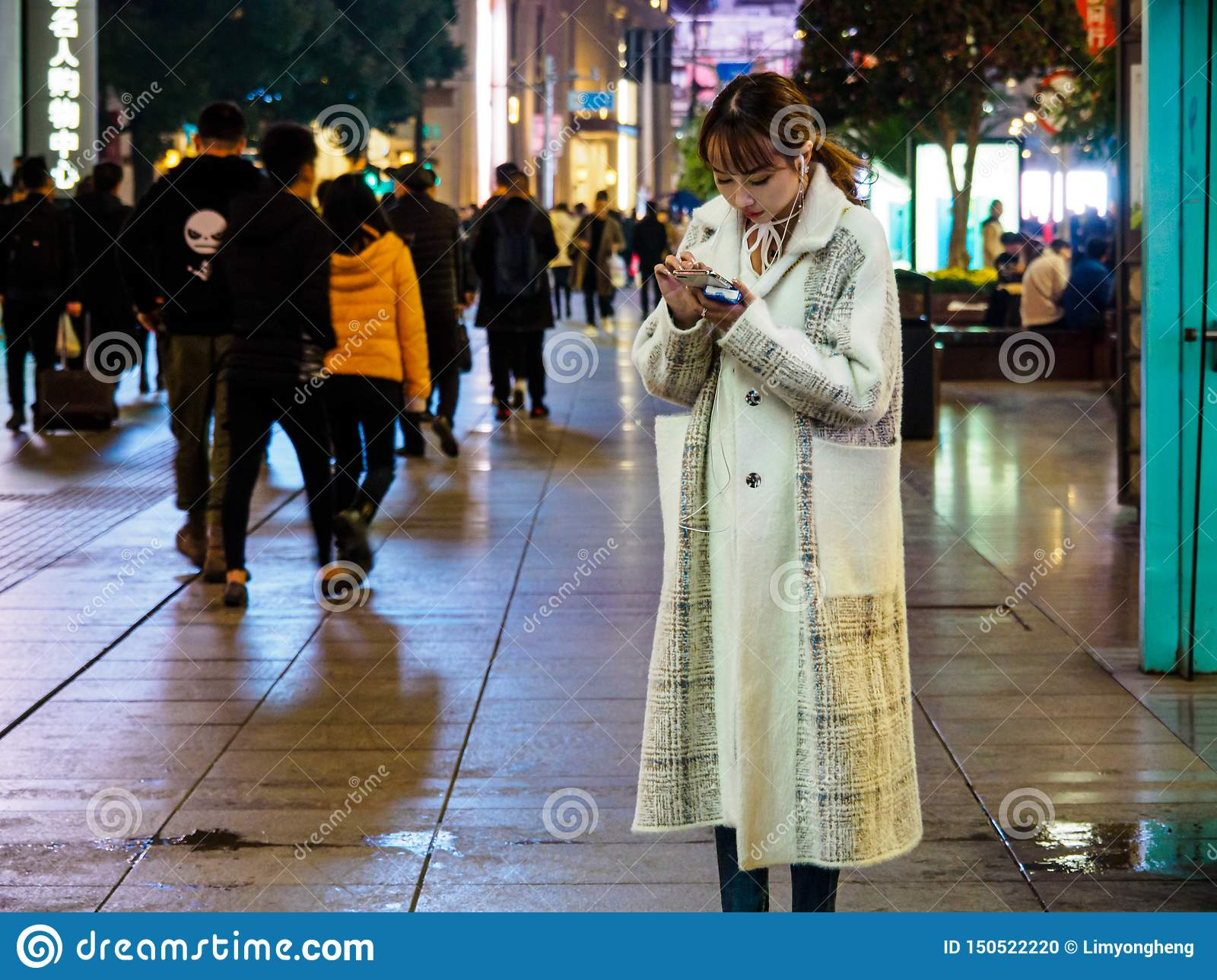 SHANGHAI, CHINA - 12 MAR 2019 –An attractive Chinese lady on her smartphone at East Nanjing Road Nanjing Dong Lu pedestrian