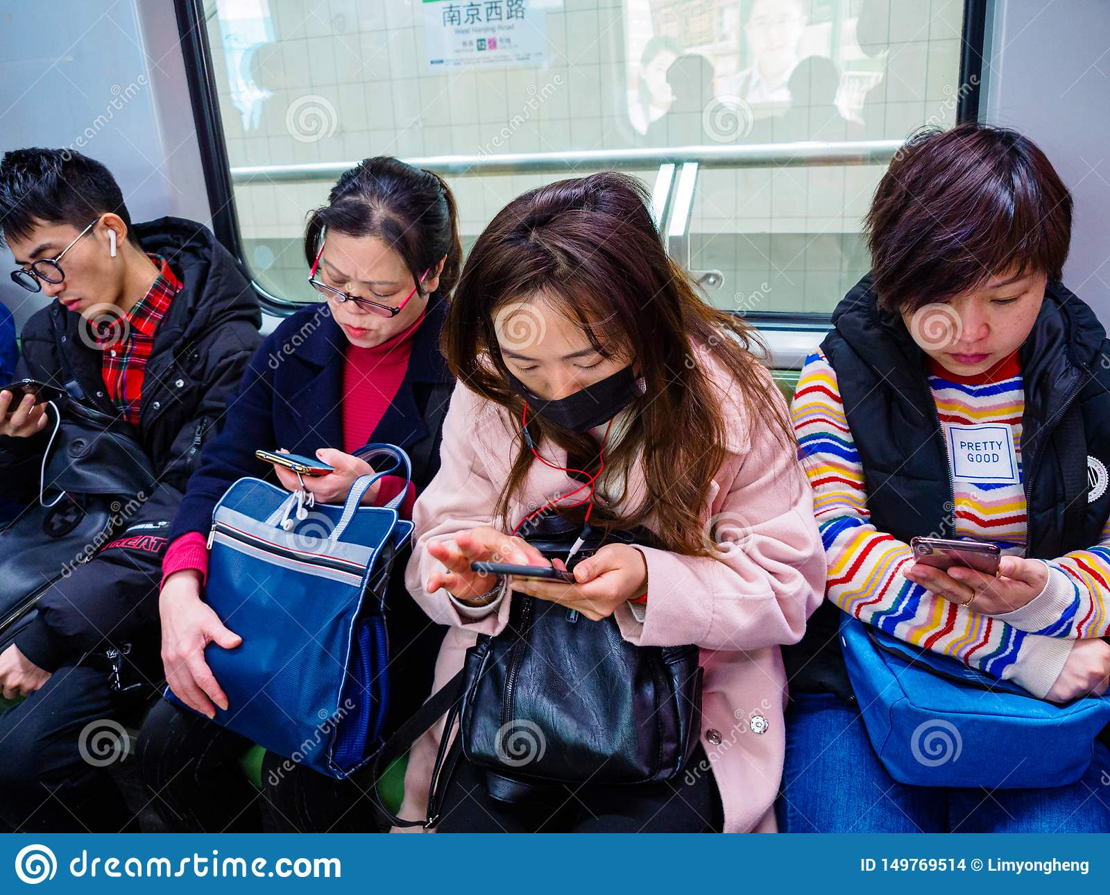 SHANGHAI, CHINA - 12 MAR 2019 - a row of commuters on the Shanghai Metro all on their smartphones. China has an extremely high