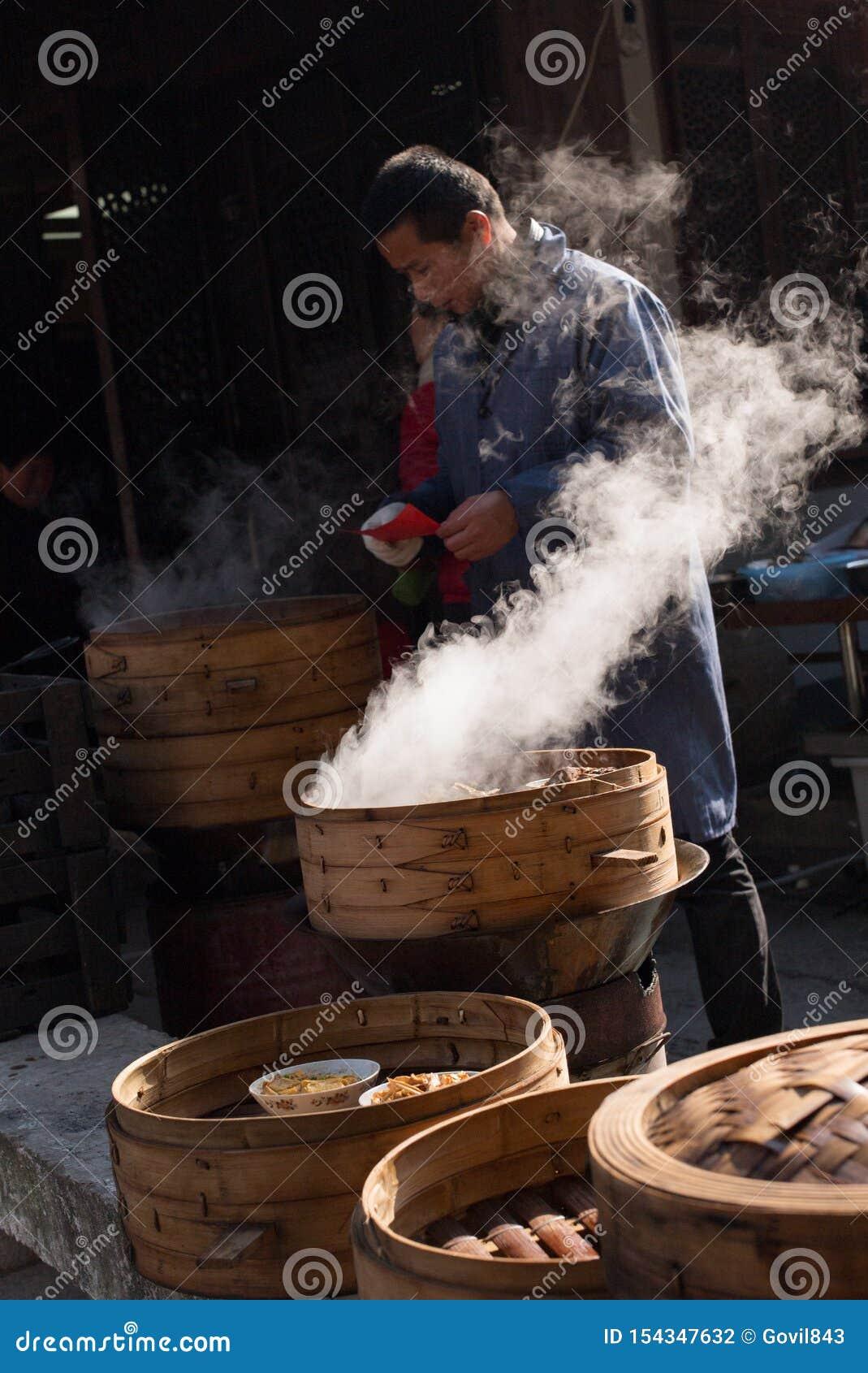 SHAOXING, CHINY: Chiński mężczyzna sprzedaje tradycyjnego lokalnego dimsum przy starym miasteczkiem Anchang podczas zimy