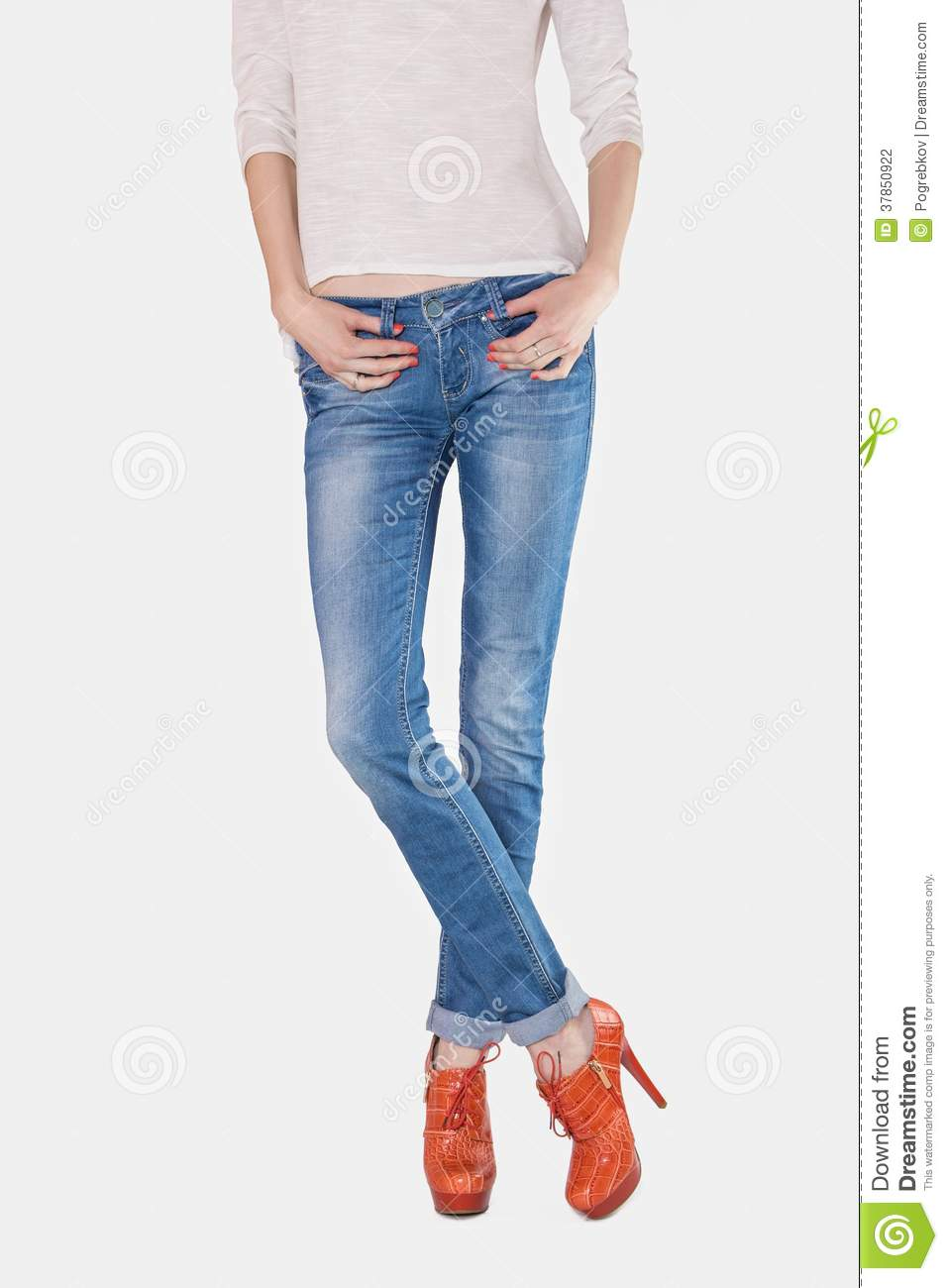 9c09c8179b Shapely female legs dressed in blue jeans and orange boots with high heels  on light background