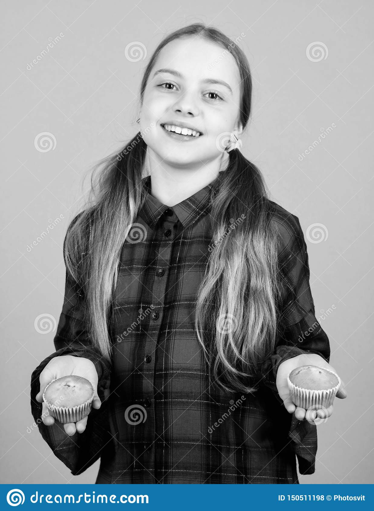 Sharing cakes for two. Happy little girl holding fairy cakes. Small child happy smiling with cup cakes. Cheerful kid