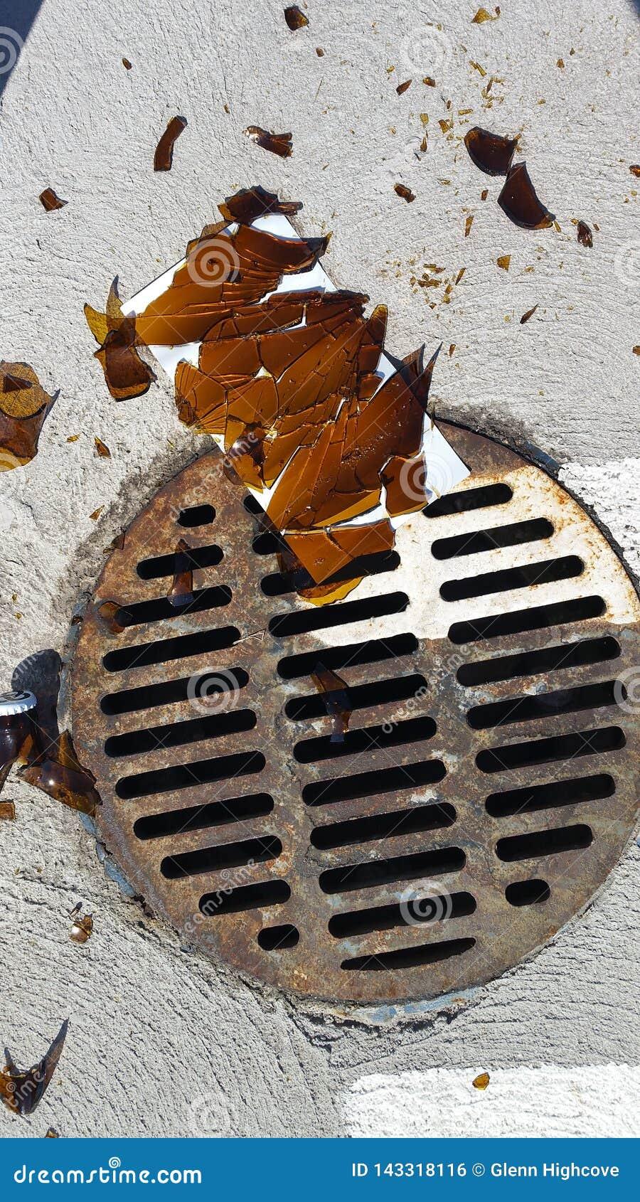 Sharp broken bottle glass by rusty storm drain in parking lot
