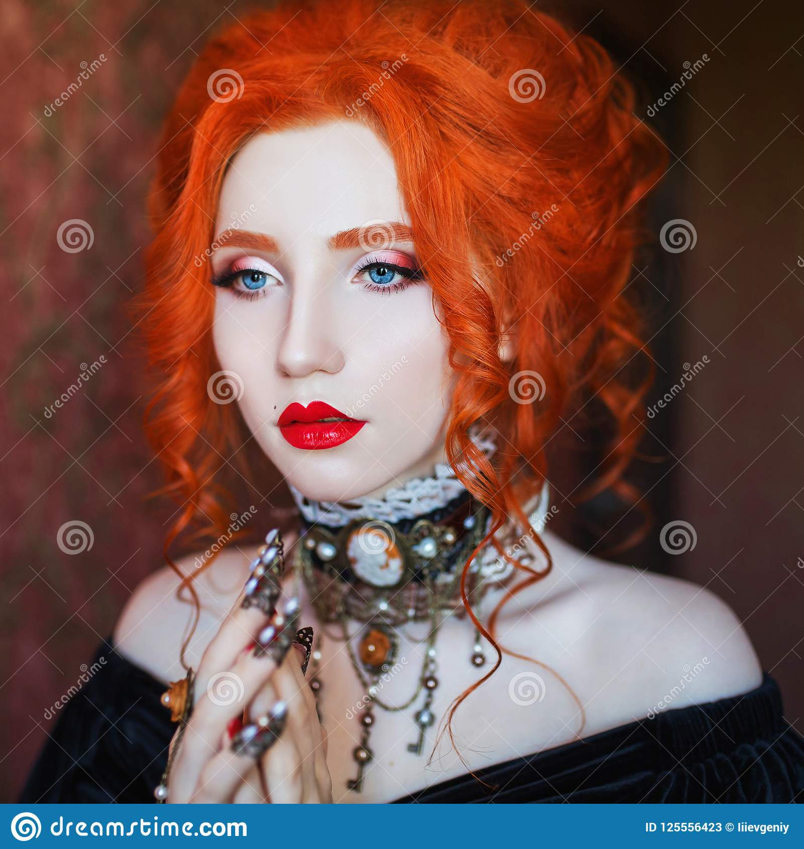 Sharp claws. Gothic halloween attire. Unusual woman pray with pale skin and red hair in black dress and necklace on neck.