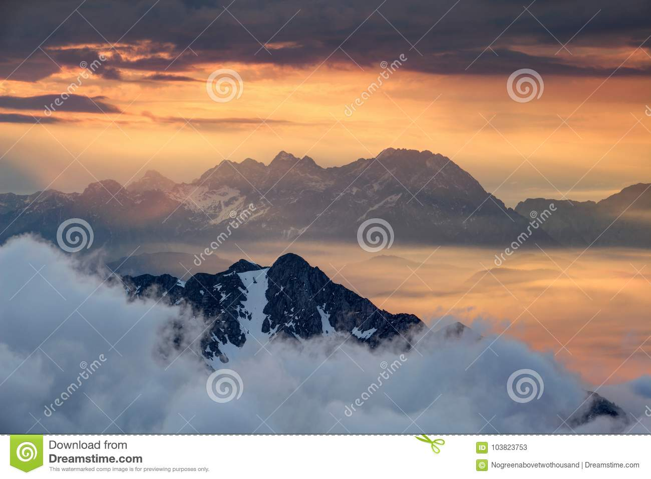 Sharp ridges above sea of clouds illuminated by rising red sun
