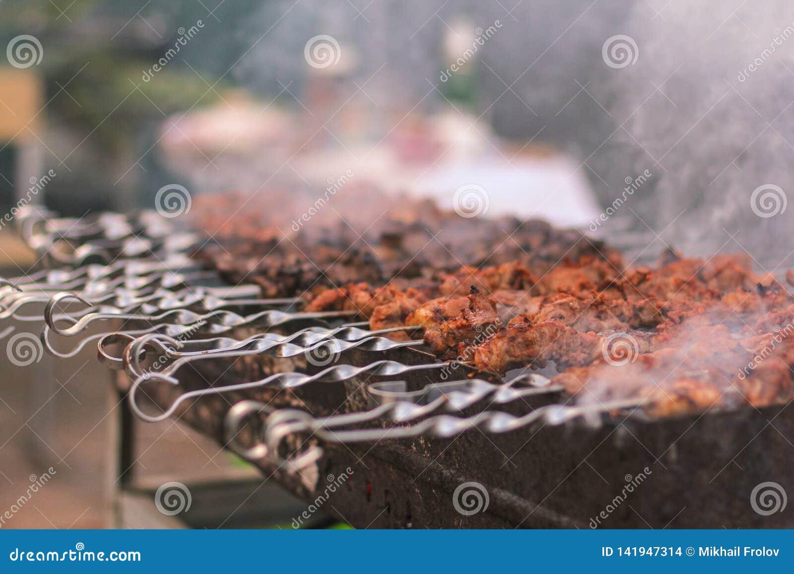 Shashlik oder shashlyk, die auf einen Grillgrill ?ber Holzkohle sich vorbereiten Gegrillte W?rfel des Schweinefleischs auf Metall