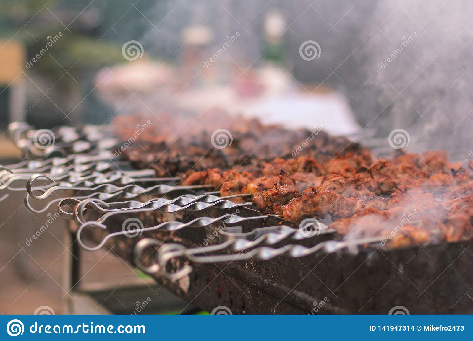 Shashlik or shashlyk preparing on a barbecue grill over charcoal. Grilled cubes of pork meat on metal skewer. Outdoor.