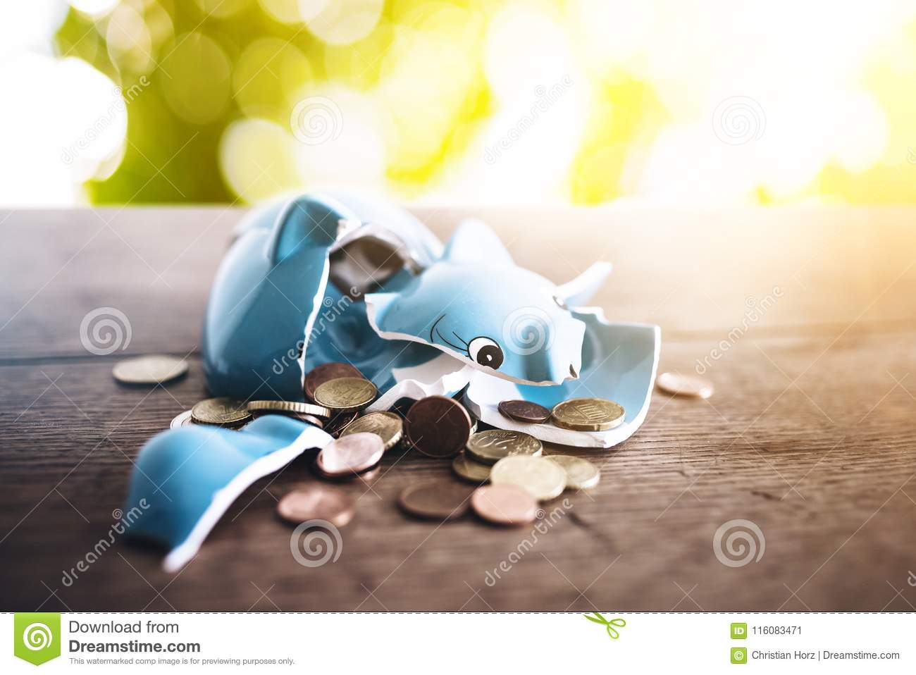 Shattered broken piggy bank with coins on rustic wooden table finance concept