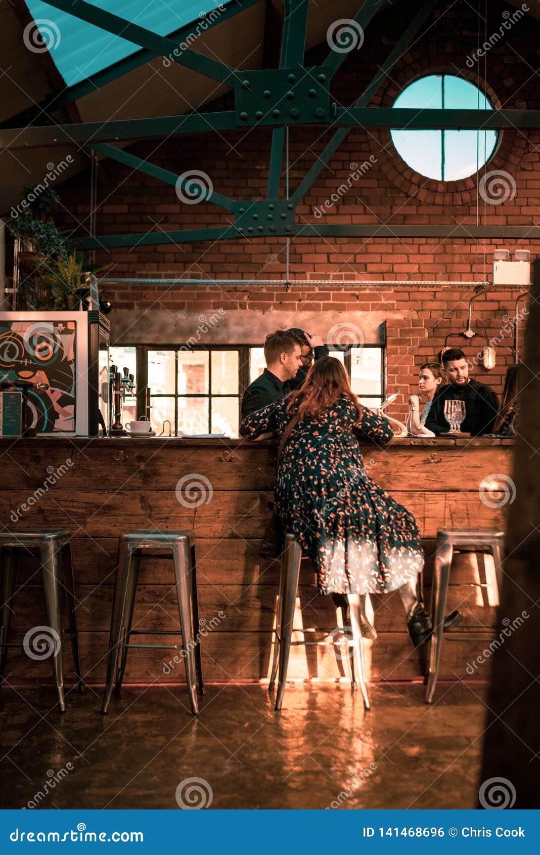 SHEFFIELD, REINO UNIDO - 9 DE DICIEMBRE DE 2018: Una mujer goza de un mediados de café del día en trabajos de los cubiertos