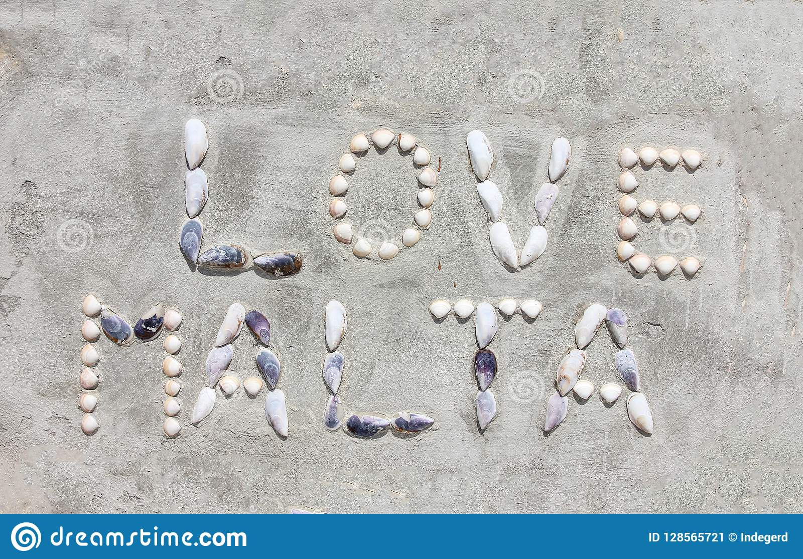 Shell letters make words Love Malta on cement wall
