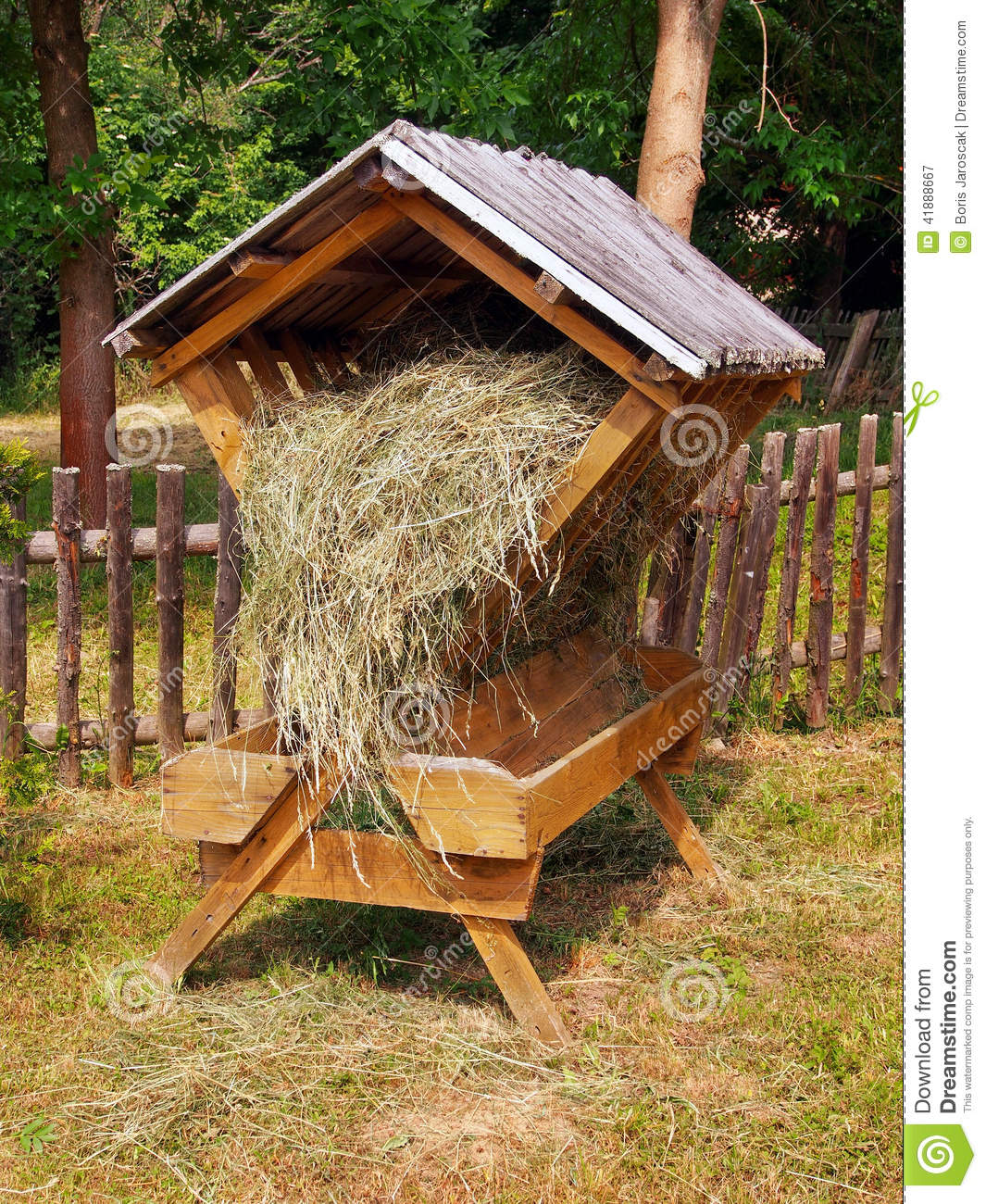 Sheltered wooden feeder fully filled with hay