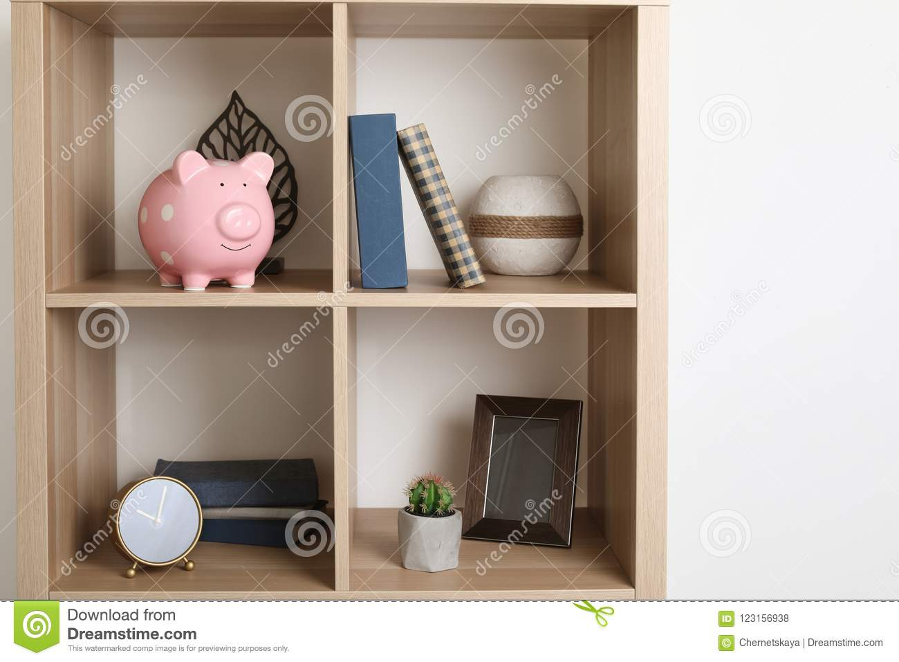 Shelving unit with decorative interior elements piggy bank near white wall