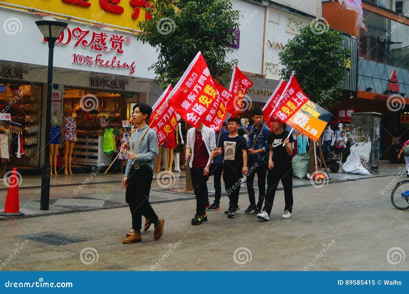 Shenzhen, China: die jungen Leute, zum der Fahne der Internet-Werbung, Werbung zu hissen geben Internet frei