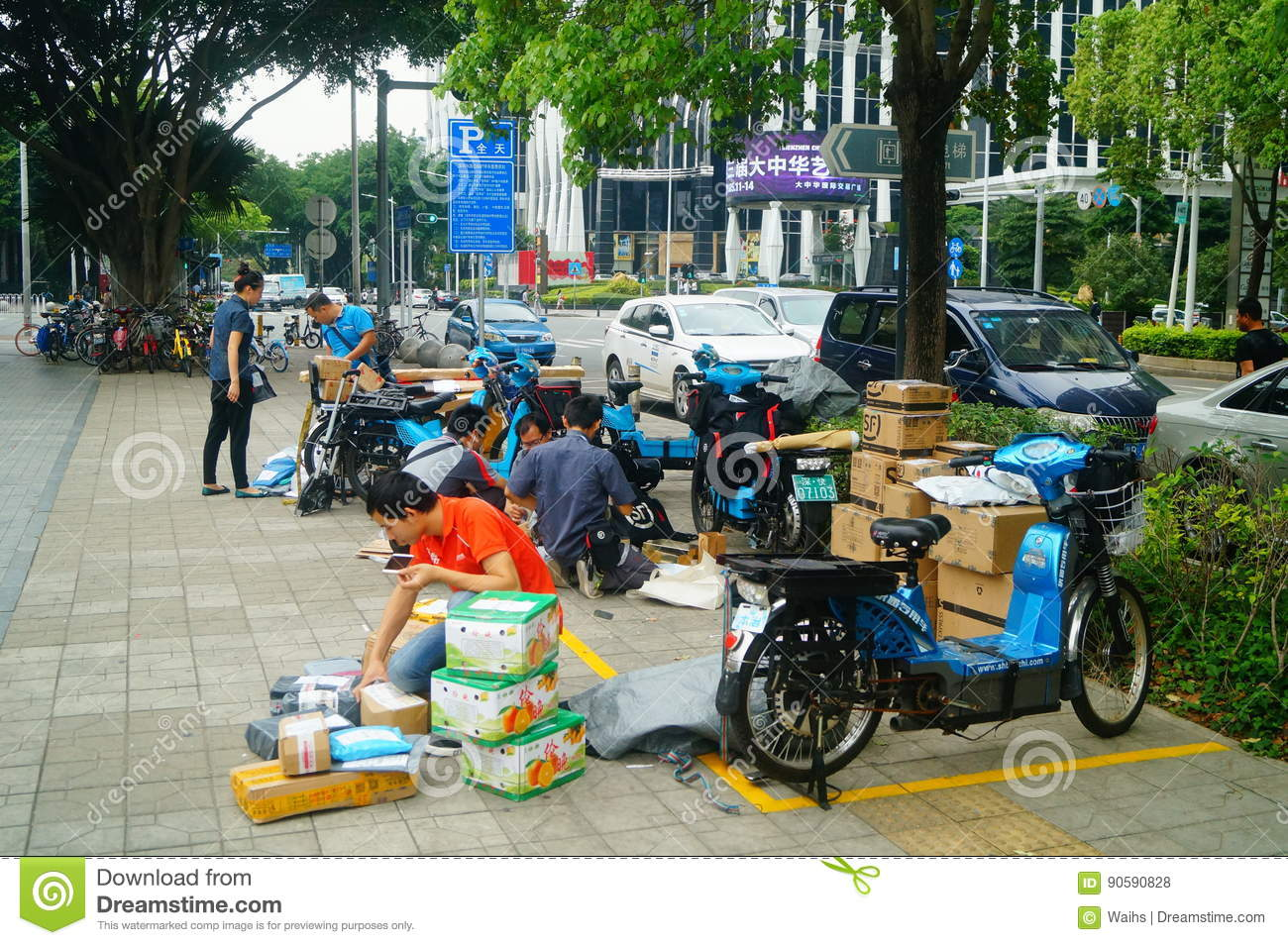 Shenzhen, China: on the sidewalk courier company employees are distributing customer courier
