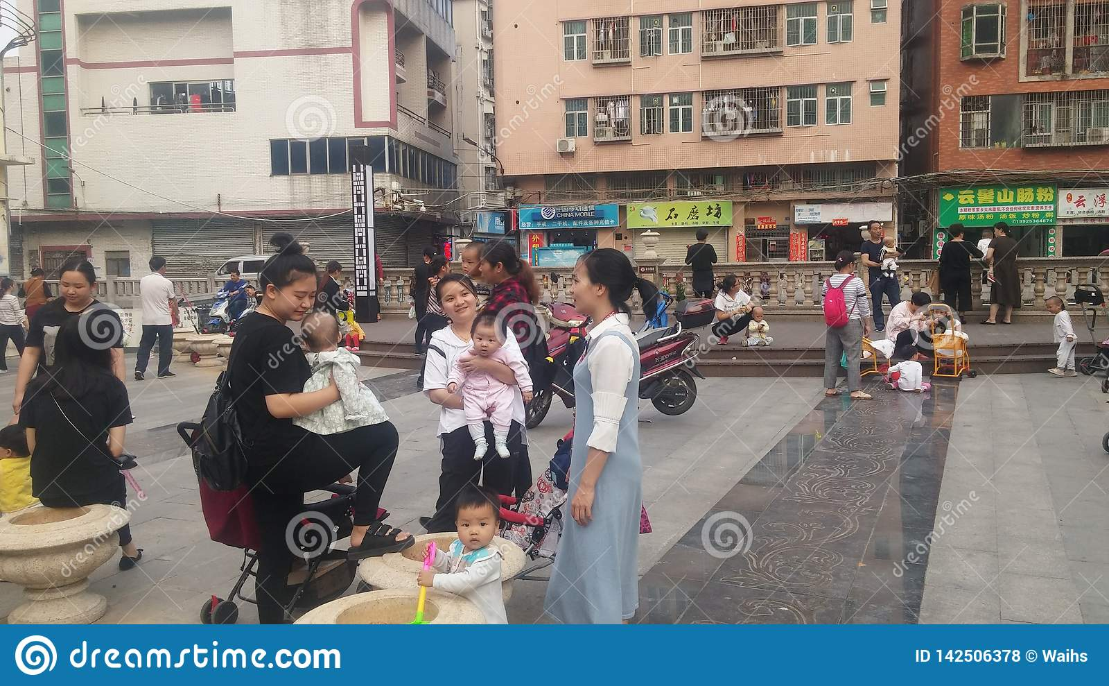 Shenzhen, Cina: Le giovani madri o nonne giocano all aperto con i loro bambini
