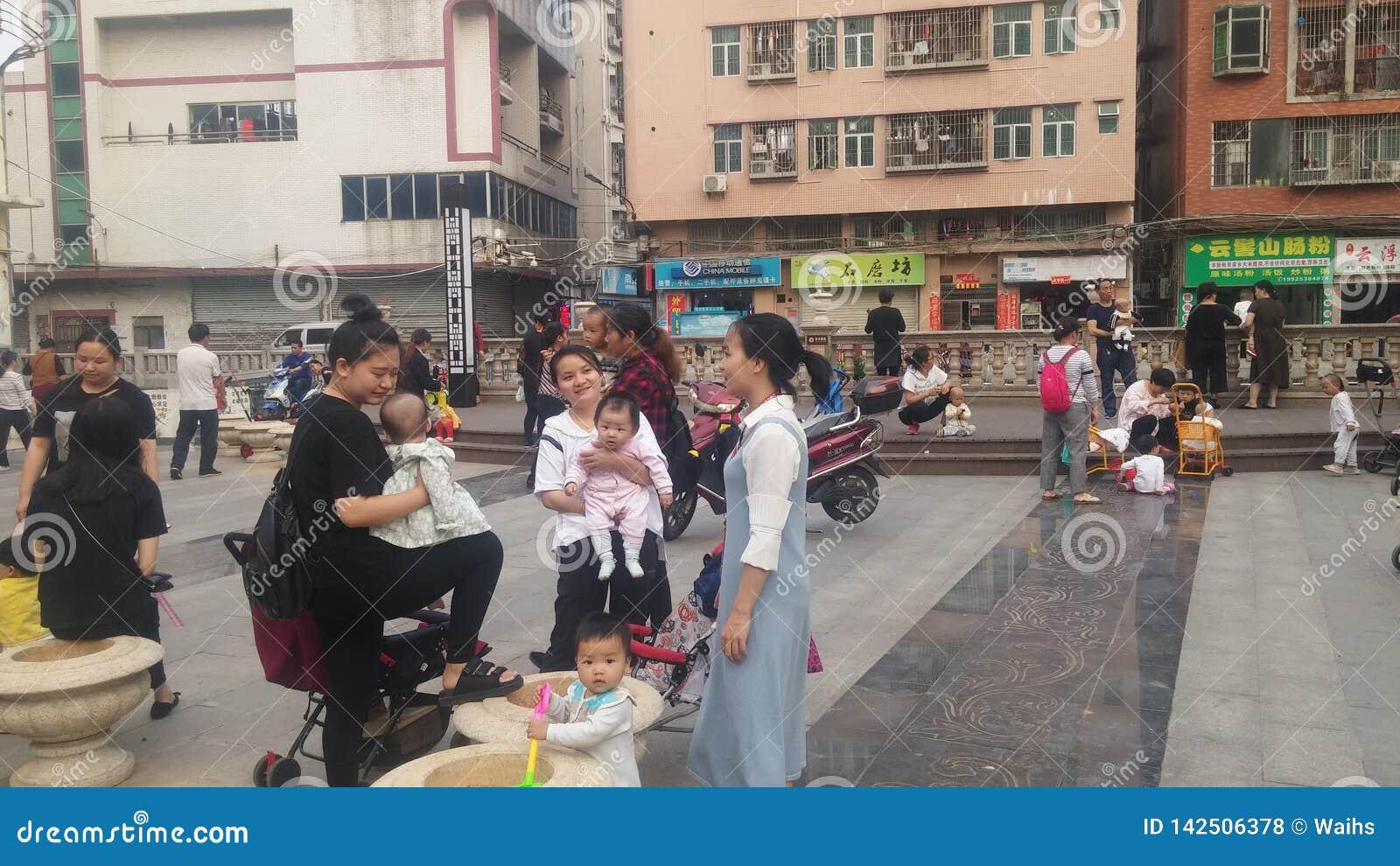 Shenzhen Kina: Unga mödrar eller farmödrar spelar utomhus med deras barn